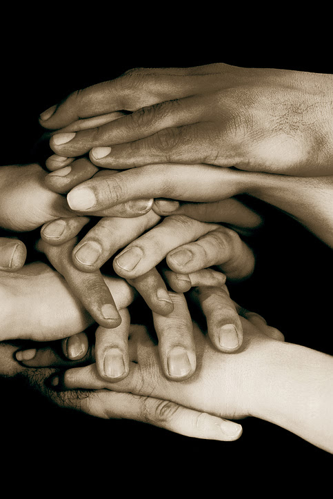 Hands stacked on top of one another on conference table, Sepia,